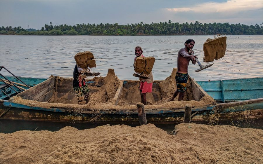 Guys shoveling sand from a boat