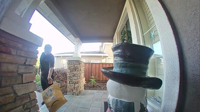 A delivery driver throwing a package