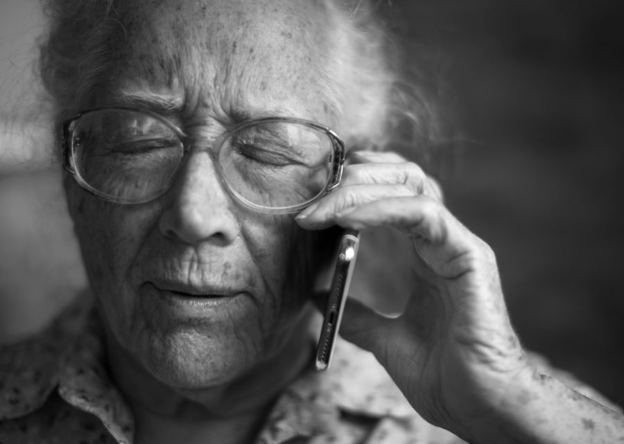 Photo of an elderly man talking on an iPhone