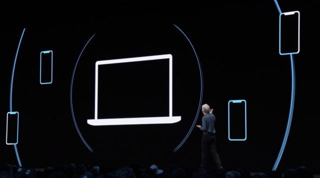 Craig Federighi in front of a screen showing an illustration of a Mac broadcasting Bluetooth keys to iOS devices.