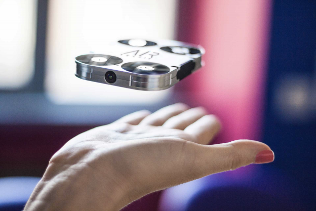 The AirSelfie camera drone hovering over a hand.