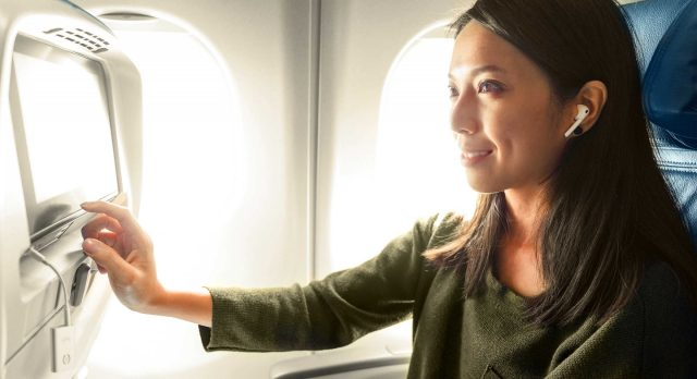 A lady using the AirFly in an airplane.