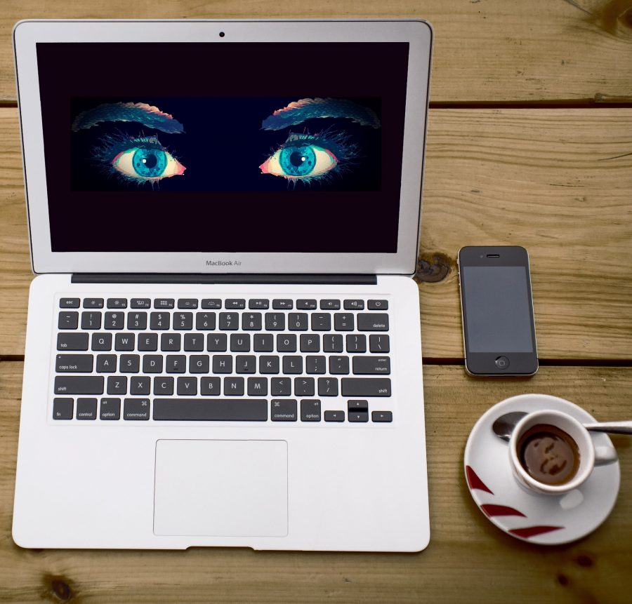 A MacBook Air with creepy eyes on the screen, an old iPhone, and an espresso.