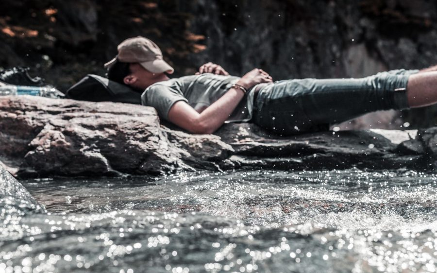 A guy sleeping in a stream.