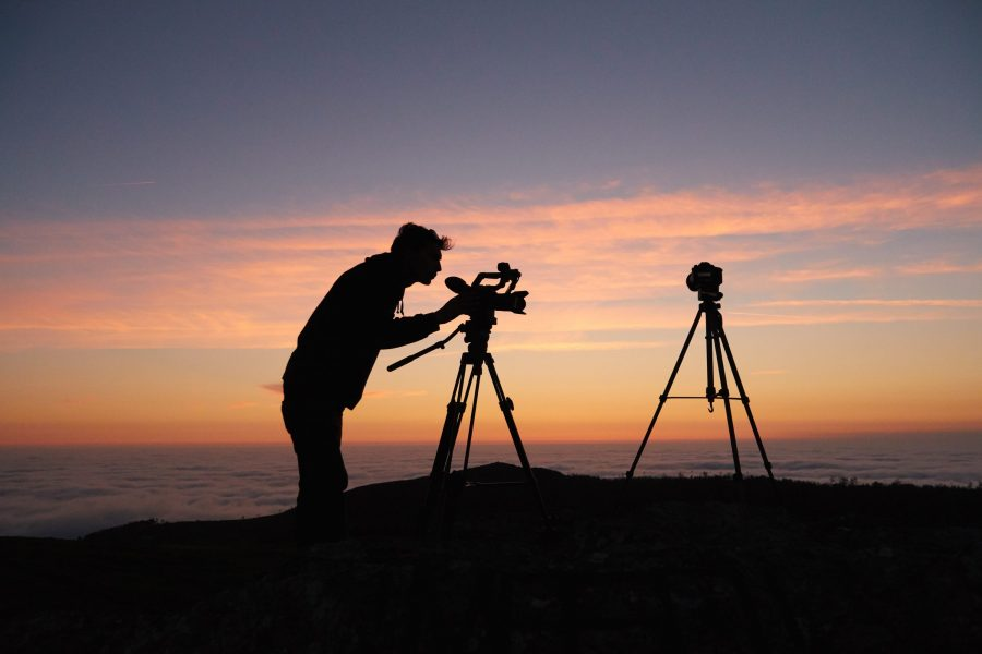 A photographer with a tripod at sunset.