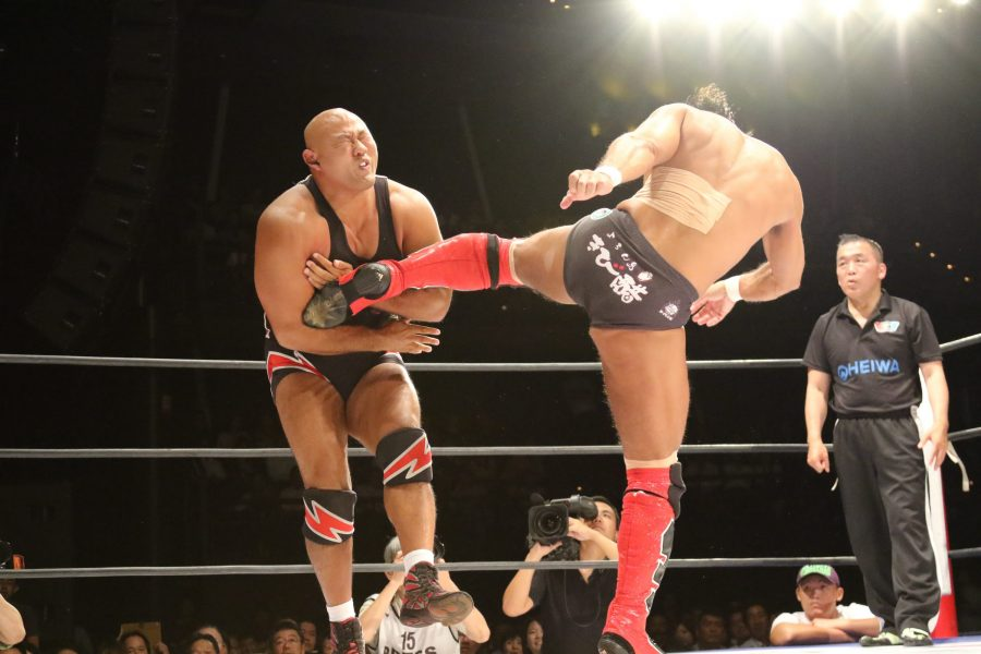 Large man kicking another large man