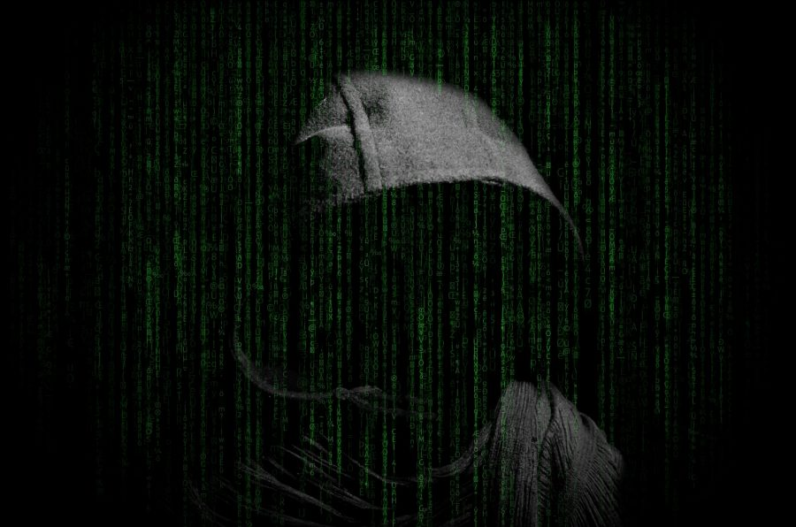 Photo of a hooded person in front of green text