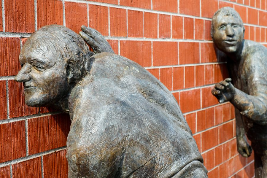 Statues listening at a brick wall