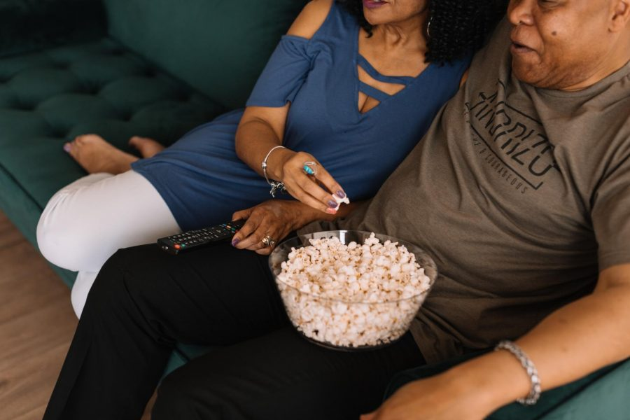 A couple eating popcorn on a couch