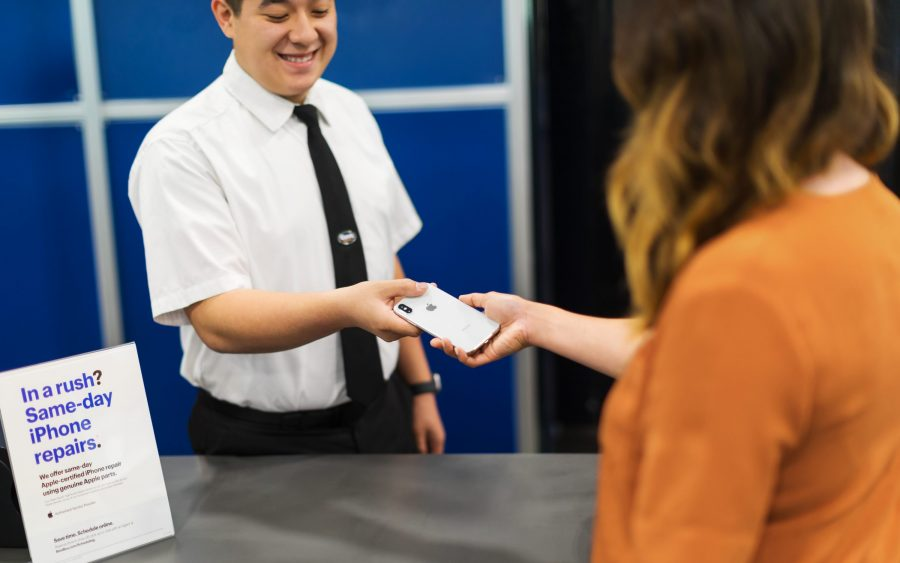 A Best Buy employee handing a phone back to a woman.